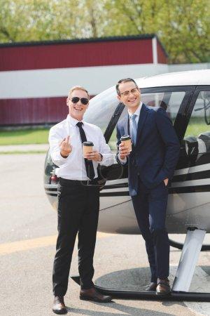 Photo pour Pilote dans des lunettes de soleil montrant le doigt du milieu et l'homme d'affaires avec le café pour aller près d'hélicoptère - image libre de droit