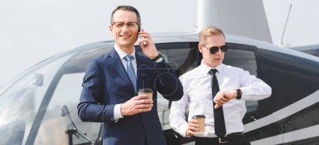 Photo for Panoramic shot of businessman with coffee to go talking on smartphone while pilot looking at watch near helicopter - Royalty Free Image