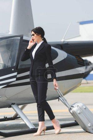 Photo pour Femme d'affaires dans l'usure formelle avec la valise parlant sur le smartphone près de l'hélicoptère - image libre de droit