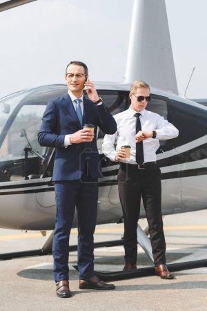 Photo pour Homme d'affaires avec du café pour aller parler sur Smartphone tandis que pilote regardant regarder près de l'hélicoptère - image libre de droit