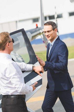 Photo pour Pilote dans l'usure formelle près d'homme d'affaires ouvrant la porte de l'hélicoptère - image libre de droit