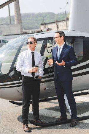 Photo pour Pilote en lunettes de soleil et homme d'affaires avec le café pour aller près d'hélicoptère - image libre de droit