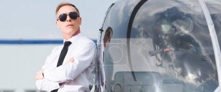 Photo pour Photo panoramique de pilote dans les lunettes de soleil et l'usure formelle avec des bras croisés près de l'hélicoptère - image libre de droit