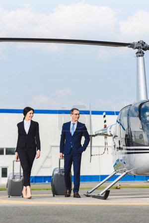 Photo for Businessman and businesswoman with suitcases near helicopter - Royalty Free Image