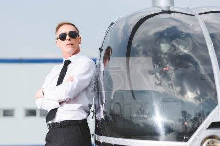 Photo for Confident Pilot in sunglasses and formal wear with crossed arms near helicopter - Royalty Free Image