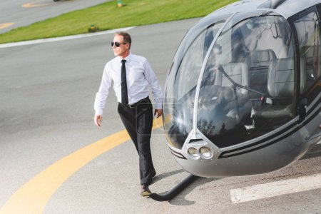 Photo for Good-looking Pilot in formal wear and sunglasses walking near helicopter - Royalty Free Image