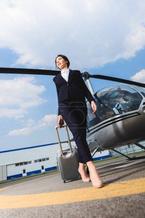 Photo pour Vue de bas angle de femme d'affaires dans l'usure formelle avec la valise près de l'hélicoptère - image libre de droit