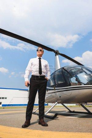 Photo pour Vue de bas angle du pilote dans l'usure formelle et les lunettes de soleil près de l'hélicoptère - image libre de droit