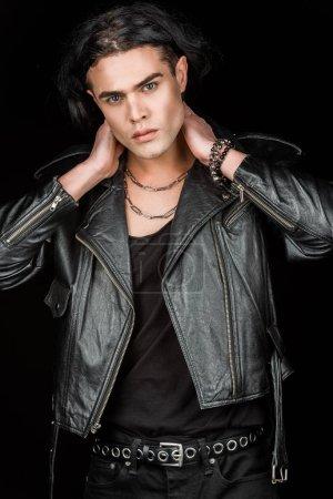 Foto de Hombre guapo en chaqueta de cuero tocando el cuello y mirando la cámara aislada en negro - Imagen libre de derechos