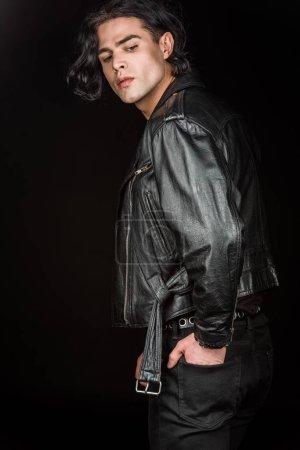 Foto de Hombre serio de pie con la mano en el bolsillo aislado en negro - Imagen libre de derechos