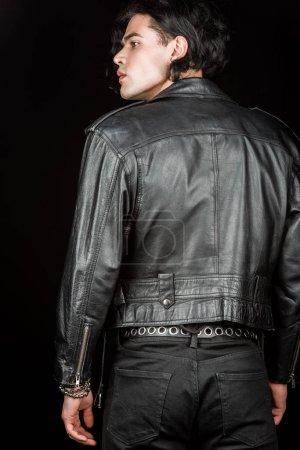 Photo pour Homme sérieux dans la veste en cuir restant dissipé sur le noir - image libre de droit