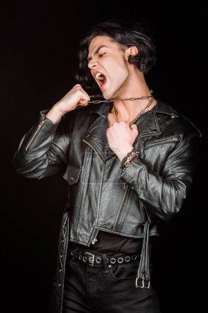 Photo pour Homme émotif touchant des chaînes sur le cou tout en criant isolé sur le noir - image libre de droit