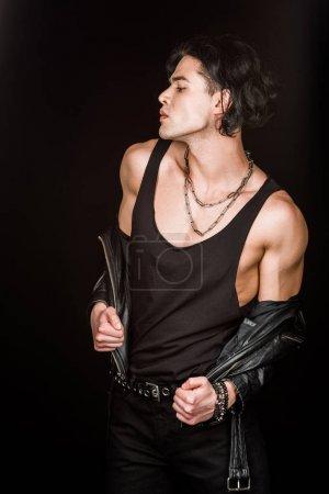 Foto de Hombre serio quitándose la chaqueta de cuero mientras está de pie aislado en negro - Imagen libre de derechos