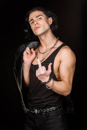 Foto de Hombre guapo mostrando el dedo medio mientras sostiene la chaqueta de cuero aislado en negro - Imagen libre de derechos