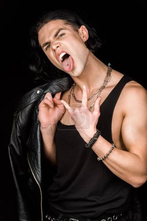 Photo for Man showing rock sign and tongue while holding leather jacket isolated on black - Royalty Free Image
