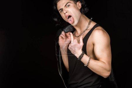 Foto de Joven que muestra el dedo medio y la lengua mientras mantiene la chaqueta de cuero aislado en negro. - Imagen libre de derechos