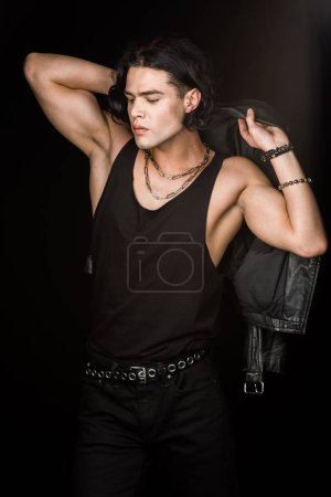 Photo for Handsome man holding leather jacket and standing isolated on black - Royalty Free Image