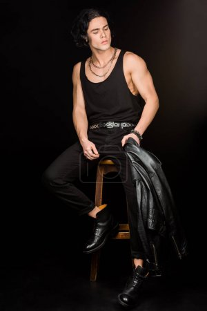 Photo for Handsome man holding leather jacket and sitting on wooden chair on black - Royalty Free Image