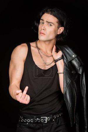 Foto de Hombre guapo mostrando el dedo medio y sosteniendo chaqueta de cuero aislado en negro - Imagen libre de derechos