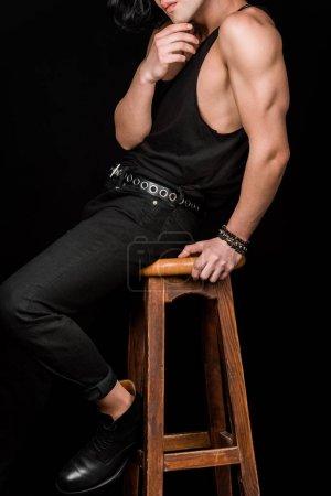 Foto de Vista recortada del hombre tocando la cara mientras se sienta en la silla aislada en negro - Imagen libre de derechos