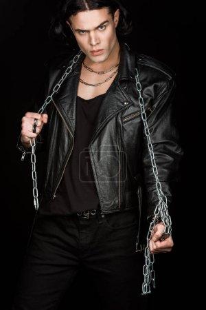Foto de Hombre guapo mirando a la cámara mientras sostiene cadenas aisladas en negro - Imagen libre de derechos