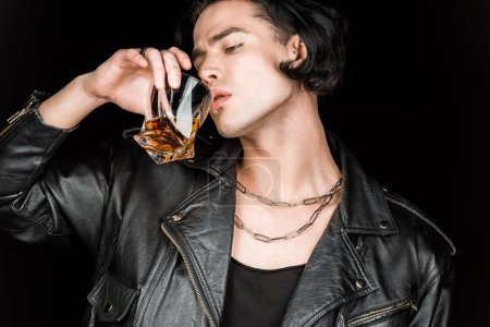 Photo for Handsome man in leather jacket drinking whiskey isolated on black - Royalty Free Image