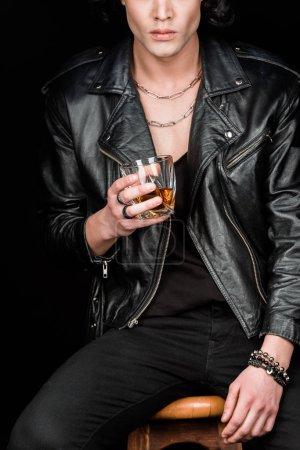 Photo pour Vue recadrée de l'homme retenant le verre de whiskey tout en s'asseyant sur la présidence en bois d'isolement sur le noir - image libre de droit