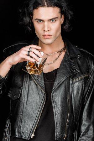Photo pour Homme sérieux retenant le verre de whiskey d'isolement sur le noir - image libre de droit