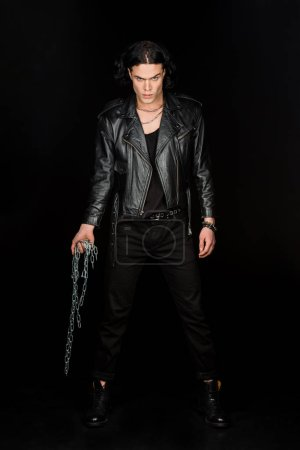 confident man looking at camera and holding chains while standing isolated on black