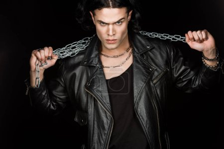 Photo for Serious man looking at camera and holding metallic chains isolated on black - Royalty Free Image