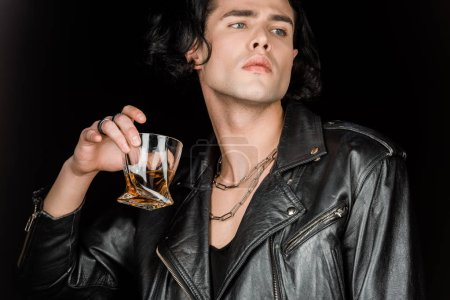 Photo for Low angle view of handsome man holding glass of whiskey isolated on black - Royalty Free Image