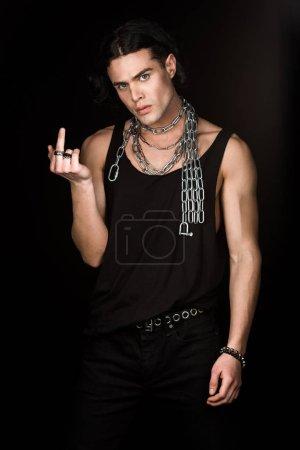 Foto de Hombre guapo con cadenas alrededor del cuello mostrando el dedo medio aislado en negro - Imagen libre de derechos