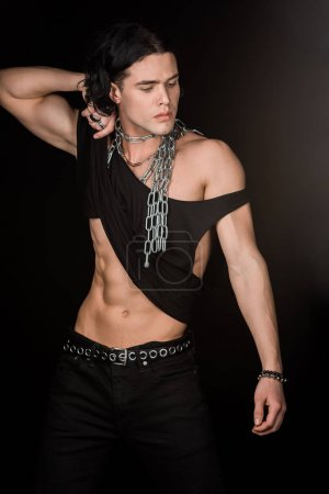 Photo for Handsome man with chains around neck touching tank top while standing isolated on black - Royalty Free Image