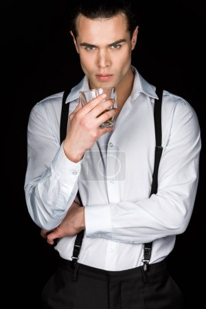 Photo for Handsome man in white shirt and suspenders holding glass of whiskey while looking at camera isolated on black - Royalty Free Image