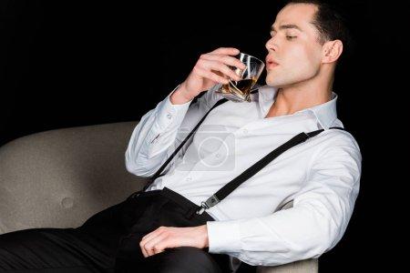Photo pour Bel homme regardant le verre de whiskey tout en s'asseyant dans le fauteuil d'isolement sur le noir - image libre de droit