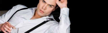 Photo pour Tir panoramique de l'homme sérieux dans la chemise blanche et bretelles retenant le verre de whiskey et regardant la caméra d'isolement sur le noir - image libre de droit