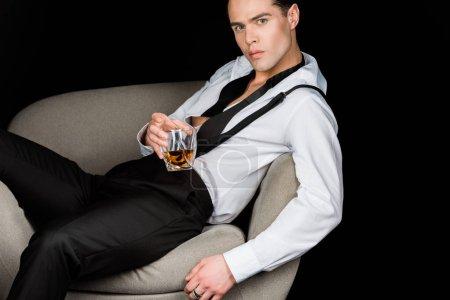 Photo pour Homme sérieux dans la chemise blanche et les bretelles retenant le verre de whiskey tout en s'asseyant dans le fauteuil isolé sur le noir - image libre de droit