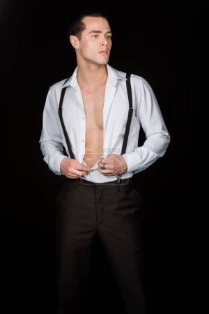 Foto de Hombre guapo tocando camisa blanca mientras está de pie aislado en negro - Imagen libre de derechos