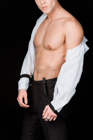 Photo for Cropped view of muscular man in white shirt and suspenders standing isolated on black - Royalty Free Image