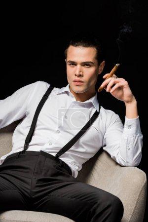 Photo pour Bel homme retenant le cigare tout en s'asseyant dans le fauteuil d'isolement sur le noir - image libre de droit