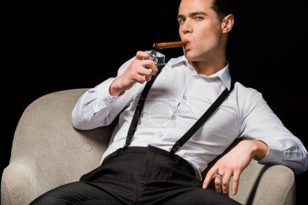 Photo pour Homme confiant retenant le briquet près du cigare tout en fumant et s'asseyant dans le fauteuil isolé sur le noir - image libre de droit