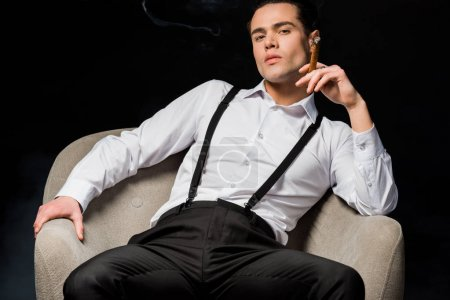Photo for Serious man holding cigar while sitting in armchair isolated on black - Royalty Free Image