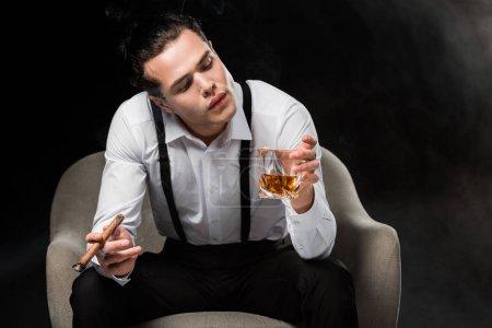 Photo pour Bel homme s'asseyant dans le fauteuil regardant le verre de whiskey et retenant le cigare sur le noir - image libre de droit