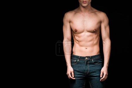 Photo pour Vue recadrée de l'homme musculaire restant d'isolement sur le noir - image libre de droit