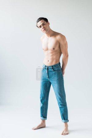 Photo pour Bel homme torse nu restant dans des jeans et regardant l'appareil-photo sur le blanc - image libre de droit