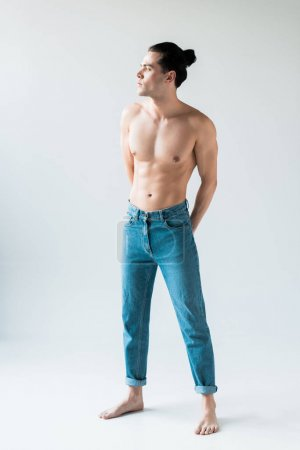 Photo for Handsome shirtless man standing in blue jeans on white - Royalty Free Image