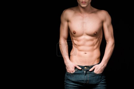 Photo for Cropped view of serious and shirtless man standing with hands in pockets isolated on black - Royalty Free Image