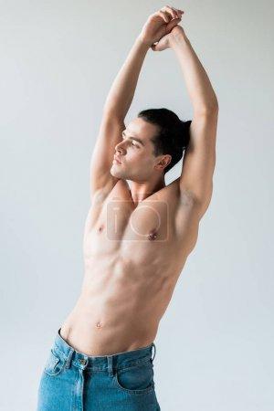 Photo pour Bel homme torse nu restant avec des mains au-dessus de la tête sur le blanc - image libre de droit