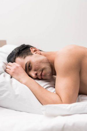 muscular man looking at camera while lying on bed at home