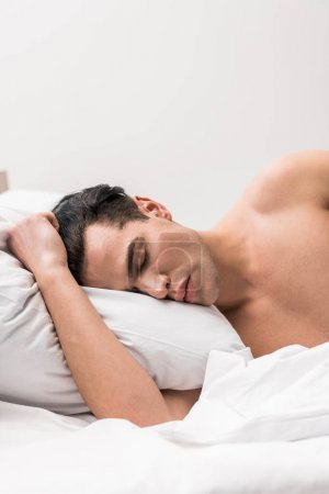 Photo for Handsome and shirtless man lying on bed with closed eyes - Royalty Free Image